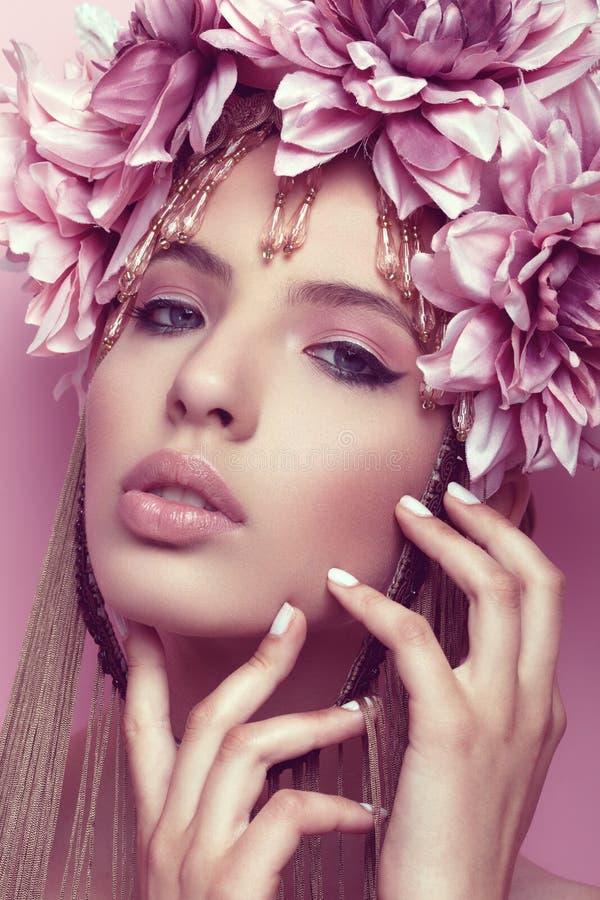 Härlig kvinna med blommakronan och makeup på rosa bakgrund arkivbild