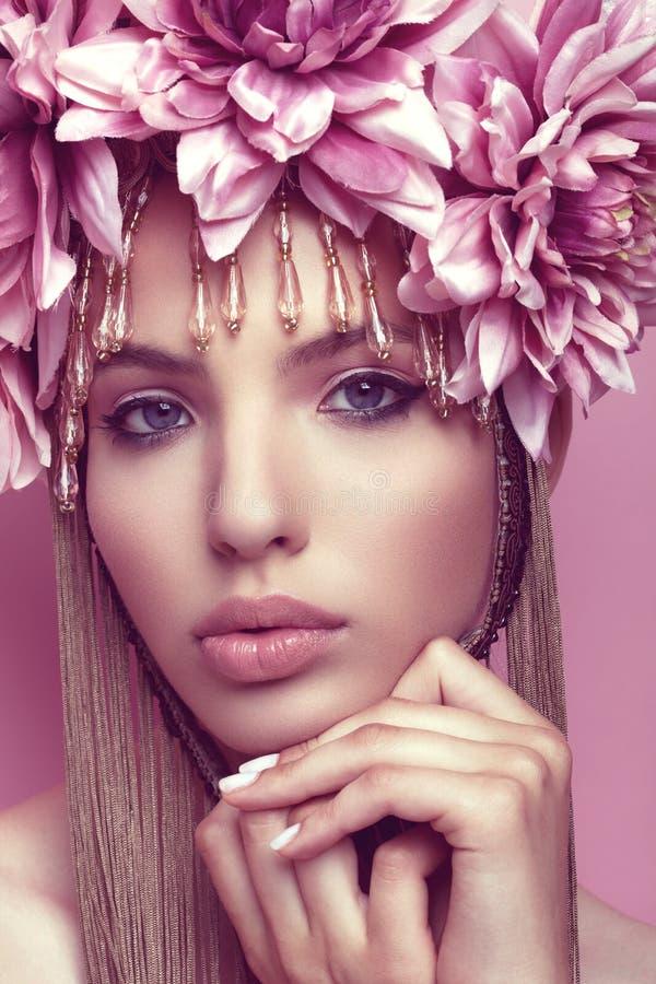 Härlig kvinna med blommakronan och makeup på rosa bakgrund arkivbilder