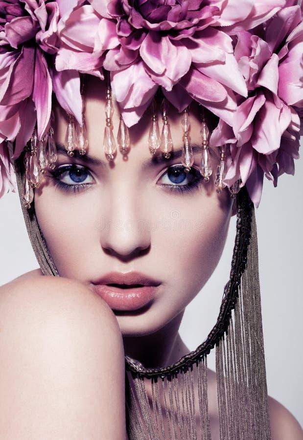 Härlig kvinna med blommakronan och makeup på vit bakgrund arkivbild
