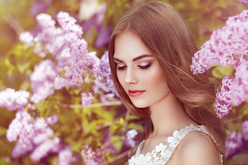 Härlig kvinna med blommor av lilan arkivbilder