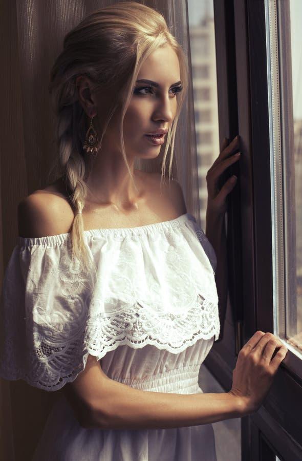 Härlig kvinna med blont hår som drömmer bredvid ett fönster royaltyfria bilder