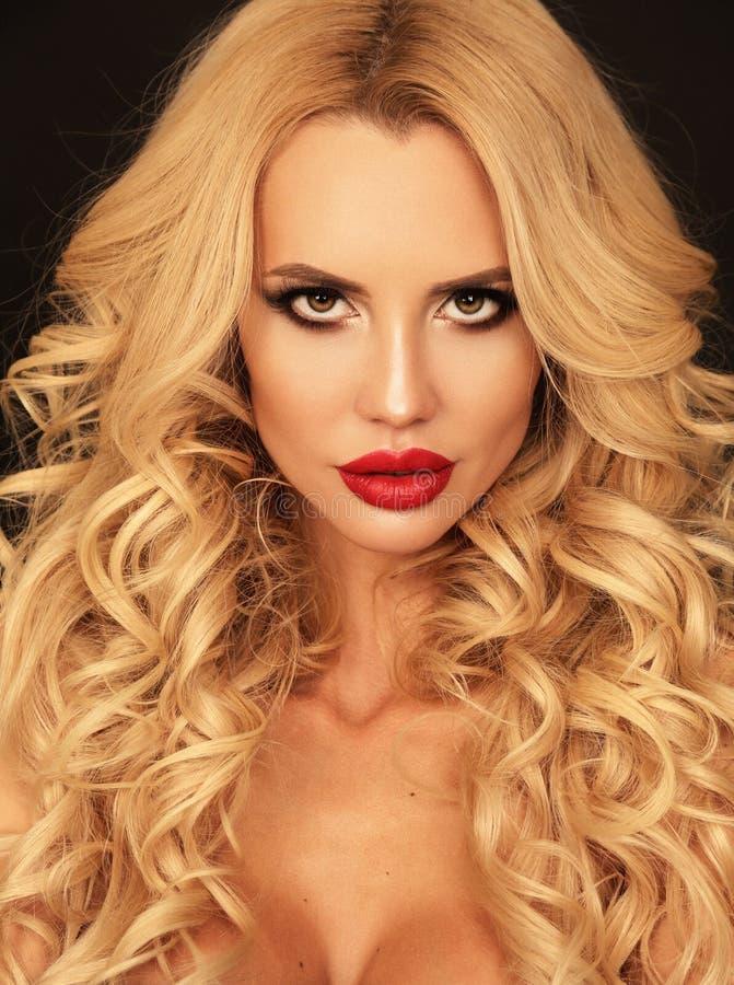 Härlig kvinna med blont lockigt hår och ljus makeup som poserar I royaltyfri bild