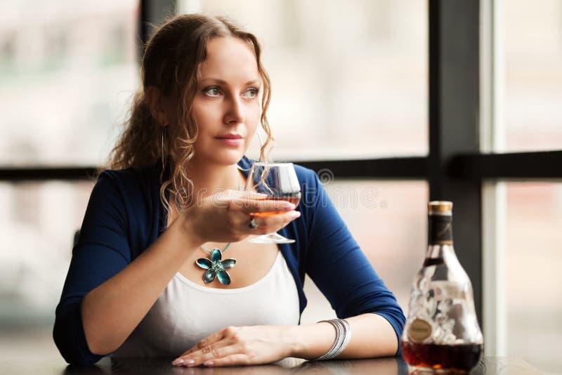 Härlig kvinna med cognacen på restaurangen royaltyfri bild