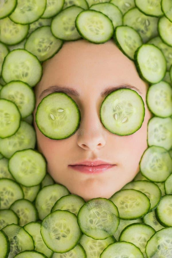 Härlig kvinna med den ansikts- maskeringen av gurkaskivor på framsida arkivfoto