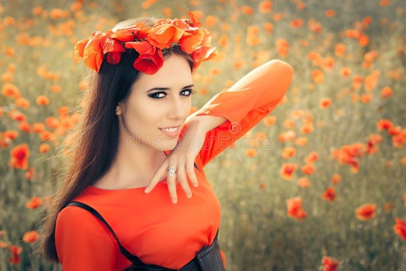 Härlig kvinna med den blom- kransen i ett fält av vallmo arkivbild