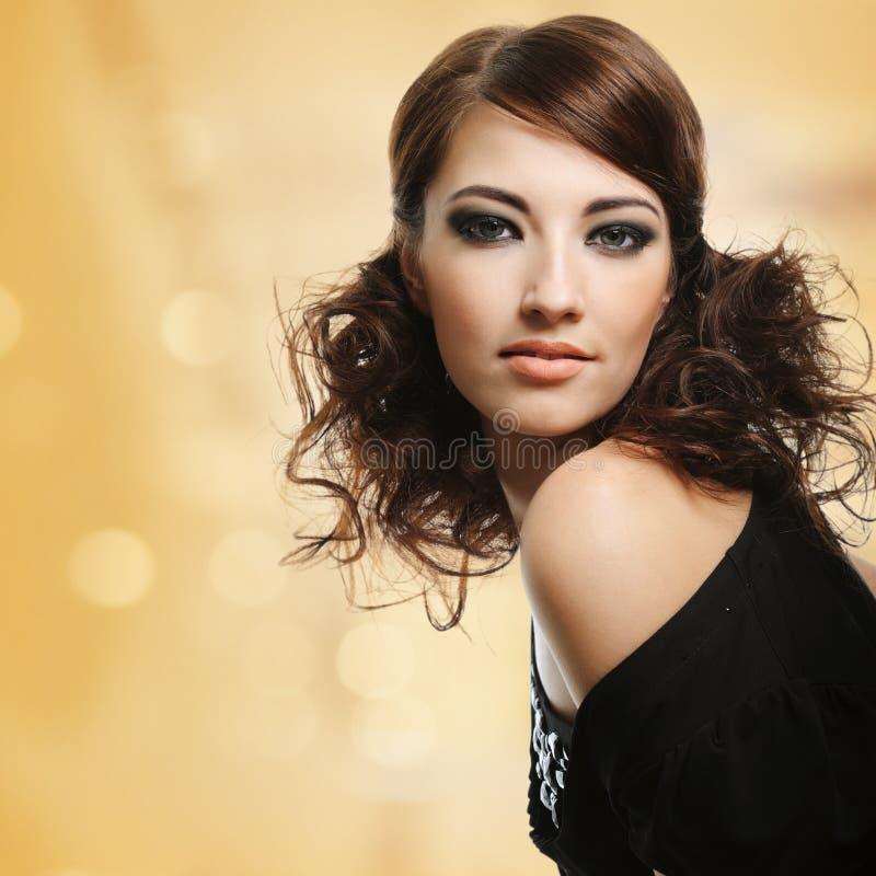Härlig kvinna med den bruna lockiga frisyren arkivbilder