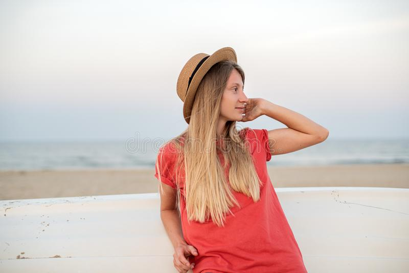 Härlig kvinna med den långa hatten för hårklädersugrör på stranden nära träfartyget royaltyfria bilder
