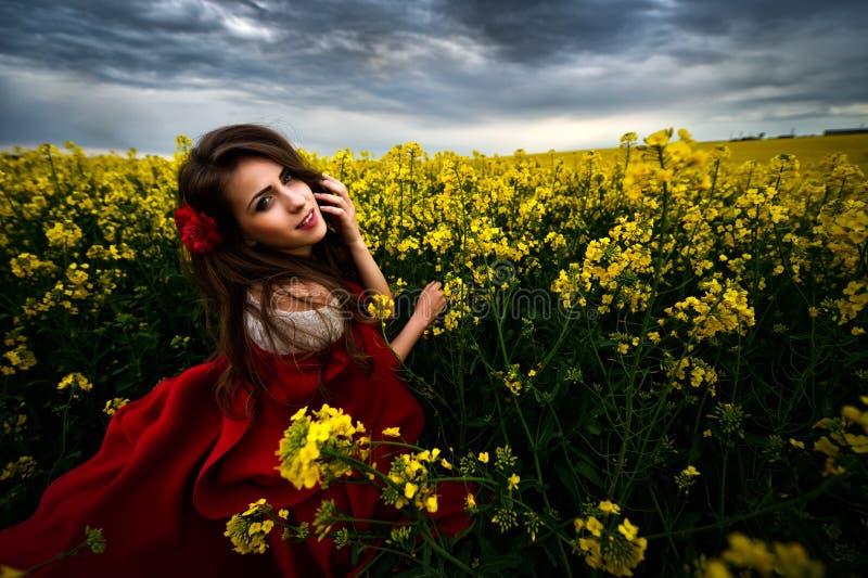 Härlig kvinna med den röda kappan i gult blommande fält arkivfoto