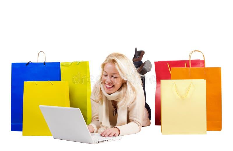 Härlig kvinna med den shoppingpåsar och bärbar dator royaltyfri foto