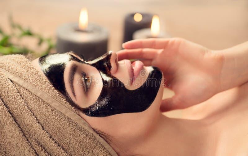 Härlig kvinna med den svarta rena svarta maskeringen på hennes framsida Skönhetmodellflicka med den svarta ansikts- avdragbara ma royaltyfri foto