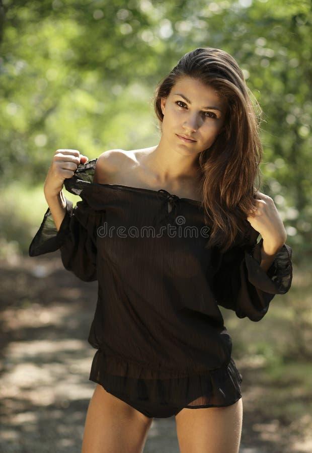 Härlig kvinna med den svarta skjortan i parkera royaltyfri bild