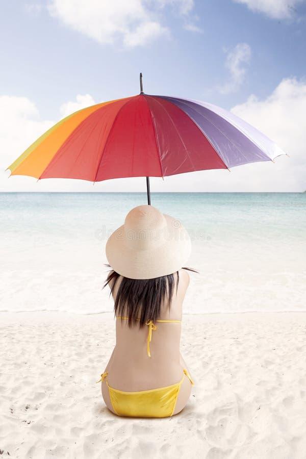Härlig kvinna med det färgrika paraplyet på stranden royaltyfria foton