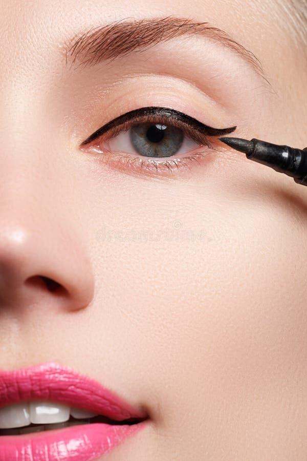 Härlig kvinna med det ljusa sminkögat med sexig svart eyelinermakeup Modepilform Chic aftonsmink Makeupskönhetintelligens arkivbilder