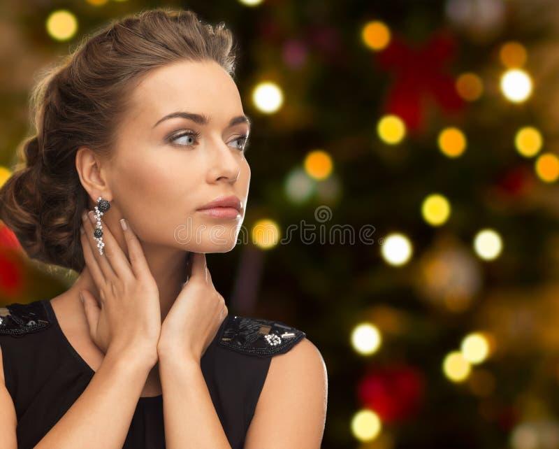 Härlig kvinna med diamantsmycken på jul fotografering för bildbyråer