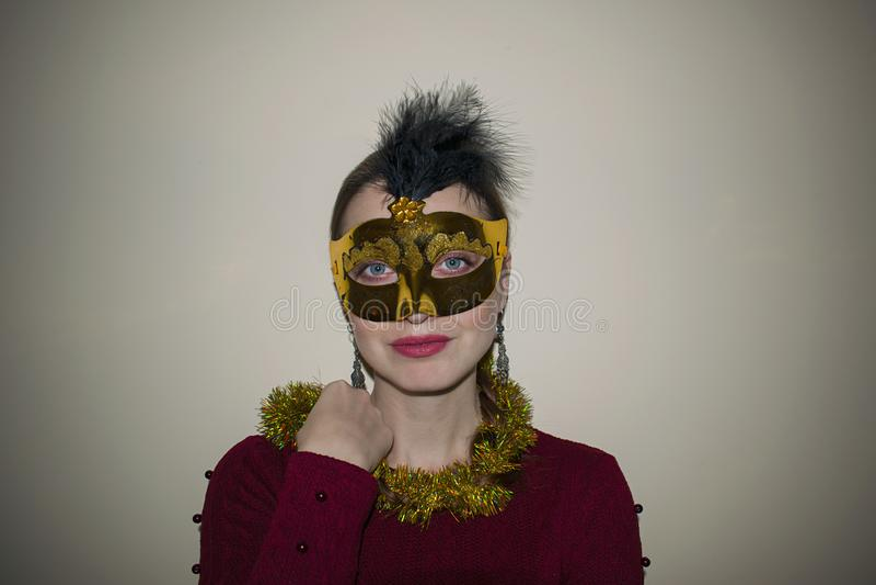 Härlig kvinna med dramatiskt smink och röd läppstift i en gul maskering arkivbild