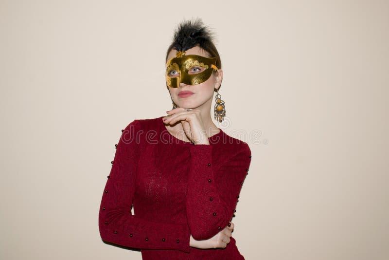 Härlig kvinna med dramatiskt smink och röd läppstift i en gul maskering arkivbilder
