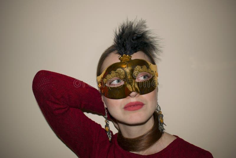 Härlig kvinna med dramatiskt smink och röd läppstift i en gul maskering arkivfoton
