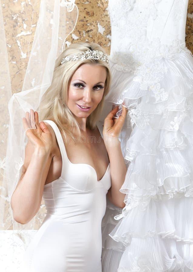 Härlig kvinna med en bröllopsklänning montering royaltyfri fotografi