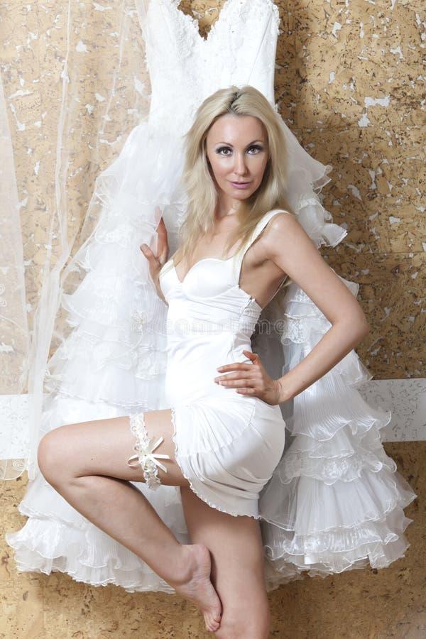 Härlig kvinna med en bröllopsklänning montering fotografering för bildbyråer