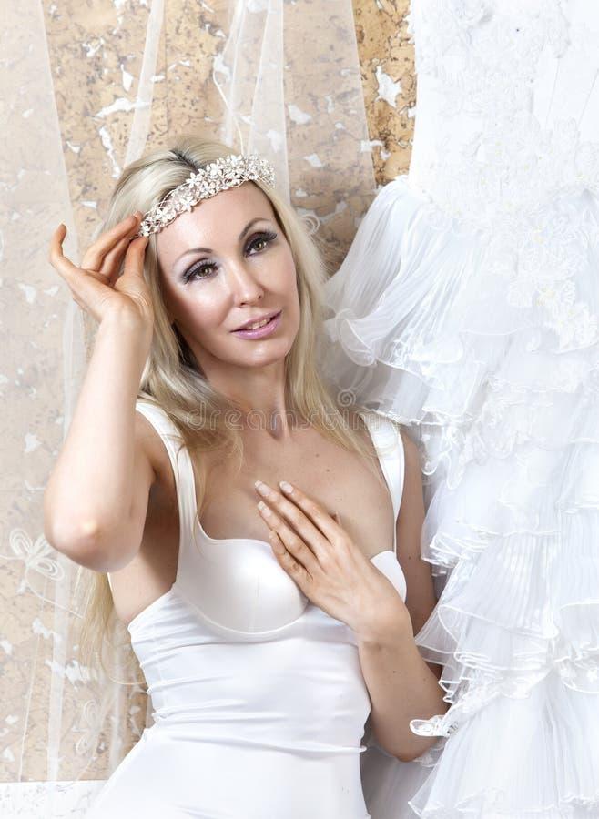 Härlig kvinna med en bröllopsklänning montering royaltyfria foton
