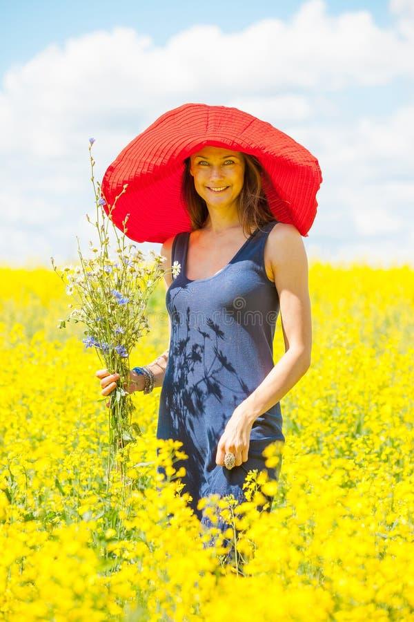Härlig kvinna med en bukett av vildblommor royaltyfri bild