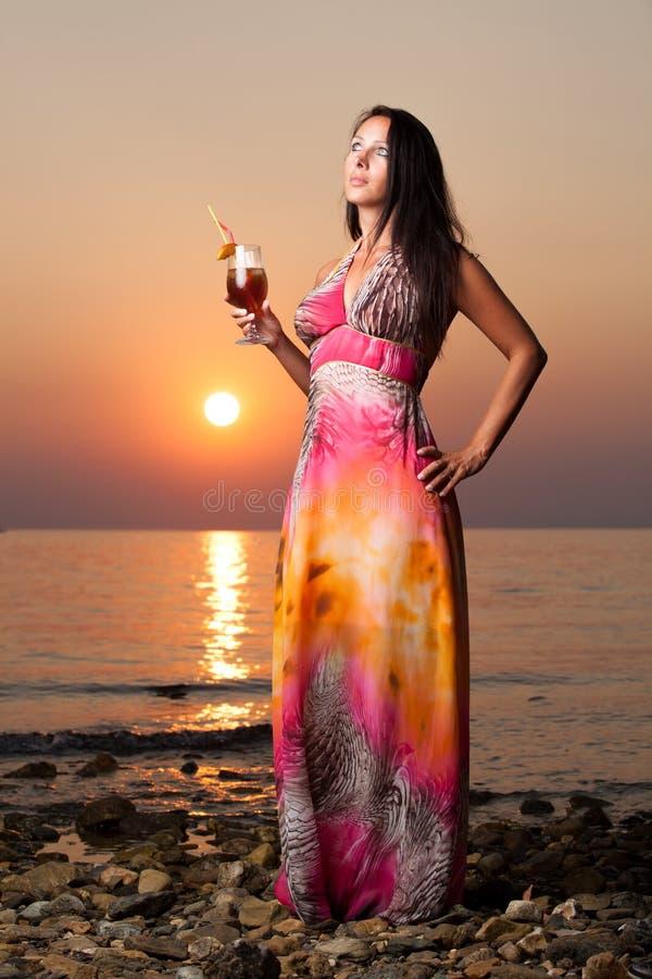 Härlig kvinna med en coctail på stranden royaltyfri bild