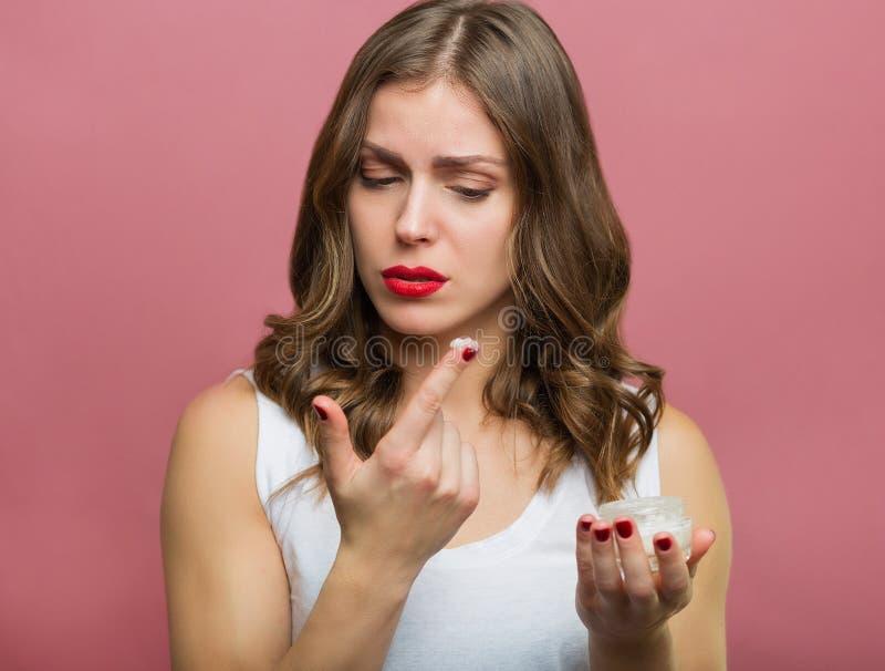 Härlig kvinna med en framsidafuktighetsbevarande hudkräm fotografering för bildbyråer