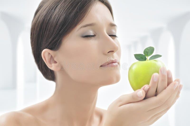 Härlig kvinna med ett äpple i henne händer royaltyfri foto
