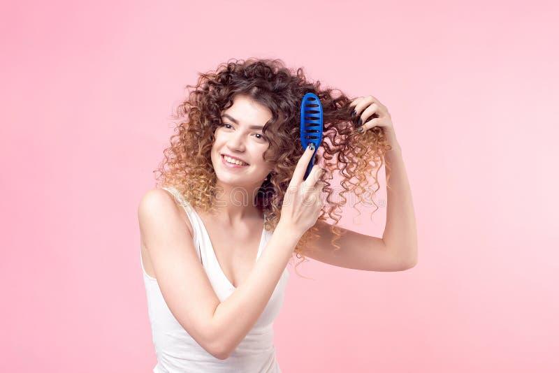 Härlig kvinna med ett leende på hennes framsida med lockigt hår i en vit T-tröja som kammar blå krullning med en blå hårkamisolat royaltyfri fotografi