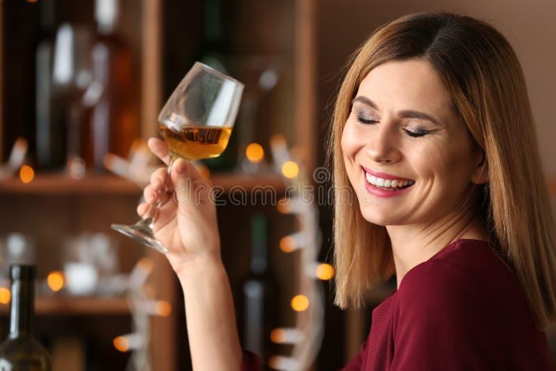 Härlig kvinna med exponeringsglas av smakligt vin i stång royaltyfri bild