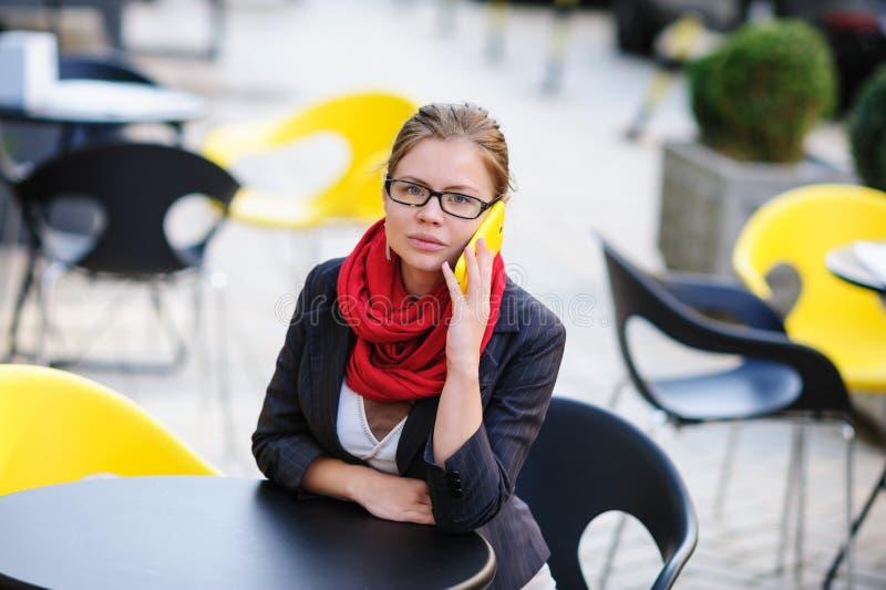 Härlig kvinna med exponeringsglas som talar på telefonen i kafét arkivfoton