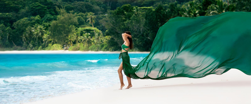 Härlig kvinna med flygtyg av Emerald Color på den tropiska ön arkivbild