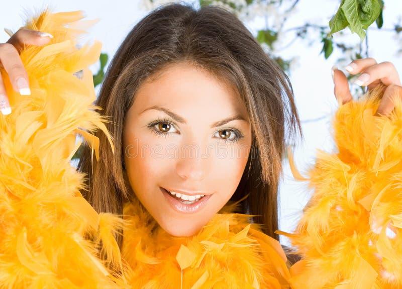 Härlig kvinna med framsidan inramning i fjädrar royaltyfri foto
