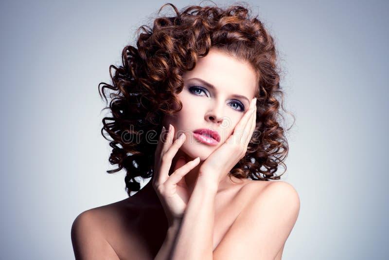 Härlig kvinna med glamourmakeup och den stilfulla frisyren arkivfoto