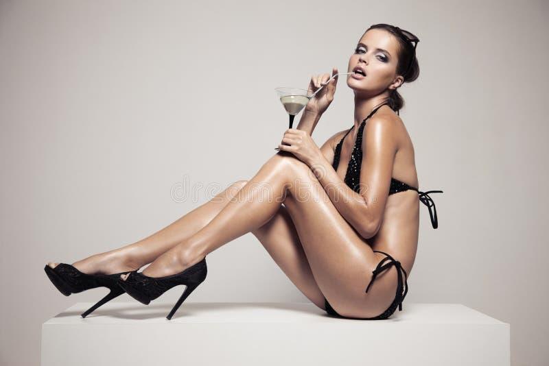 Härlig kvinna med glamoursmink i stilfull svart swimwear Drinkexponeringsglascoctail arkivbilder
