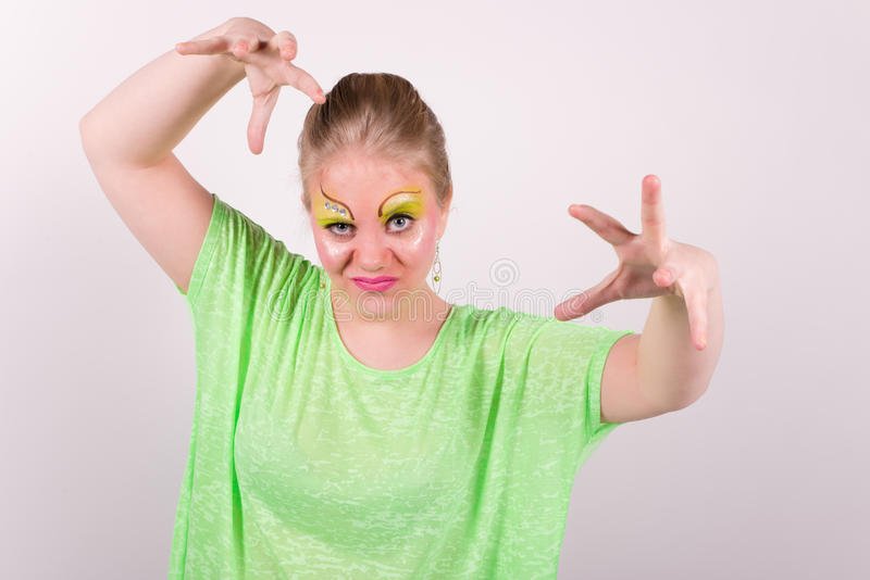 Härlig kvinna med grön makeup och kläder som casts ett pass royaltyfri fotografi