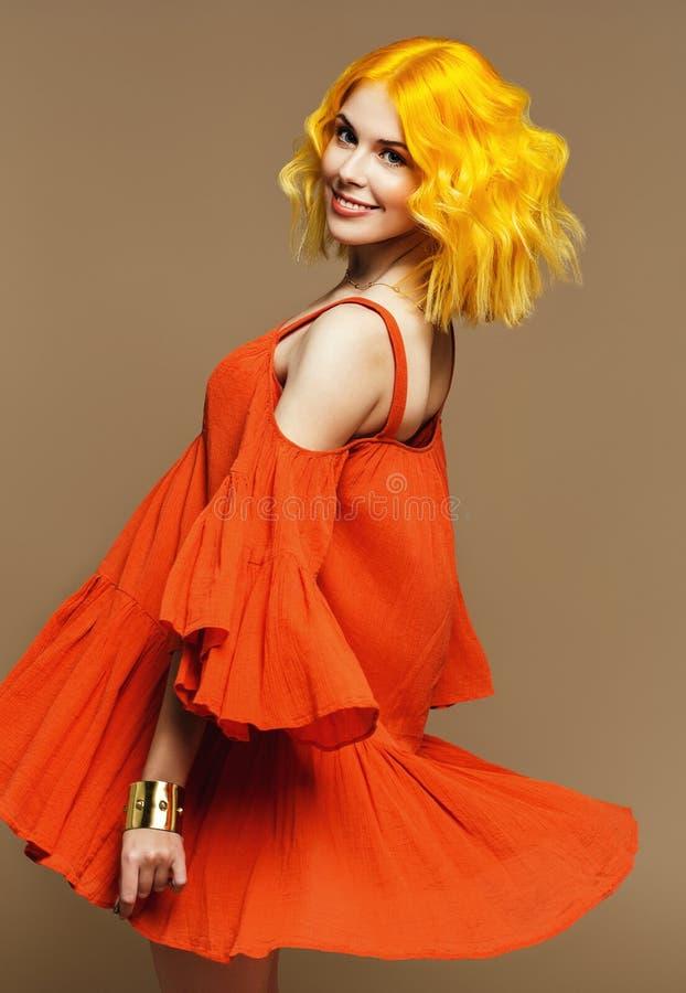 Härlig kvinna med gult hår i flödande orange klänning royaltyfri fotografi