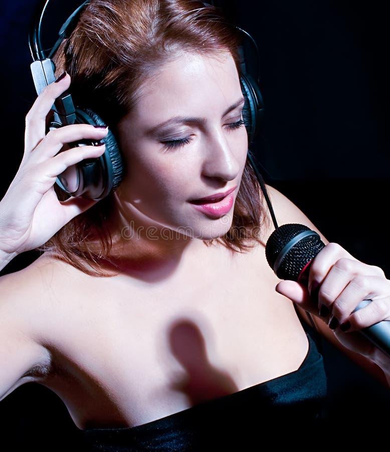 Härlig kvinna med hörlurar och att sjunga för mic arkivbilder
