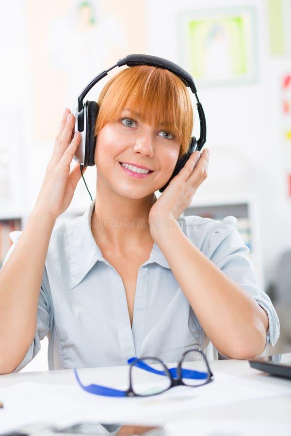 Härlig kvinna med hörlurar som lyssnar musiken royaltyfri foto