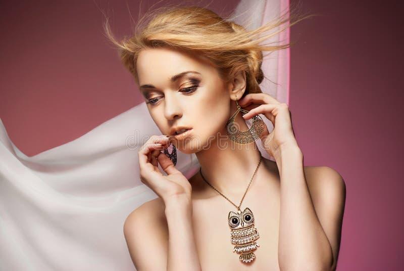 Härlig kvinna med halsbandet och örhängen royaltyfria foton