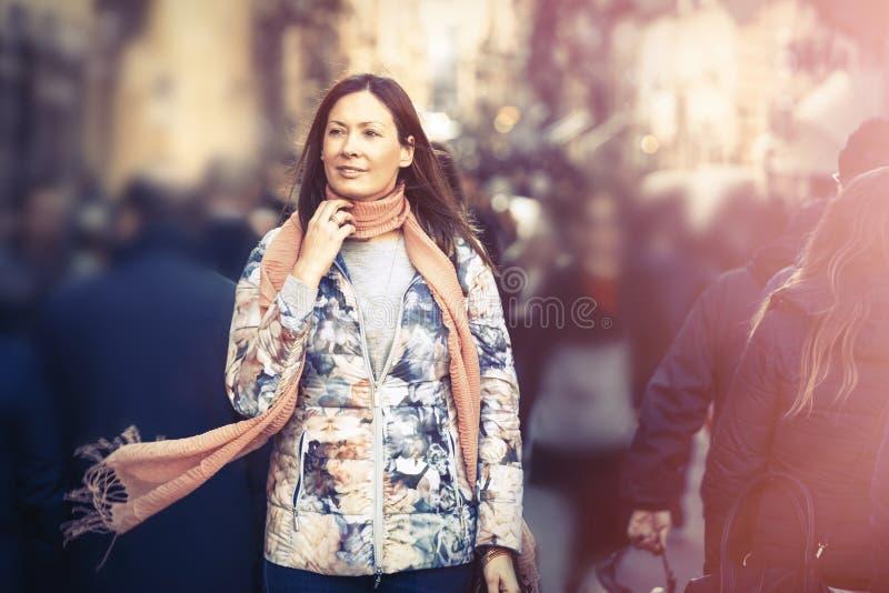 Härlig kvinna med halsduken som går i folkmassastaden timmar liggandesäsongvinter arkivbild