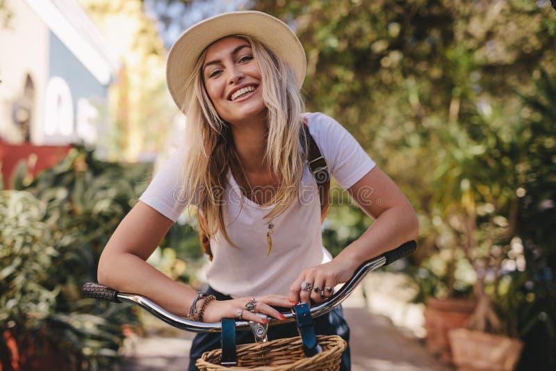 Härlig kvinna med hennes cykel utomhus royaltyfri bild