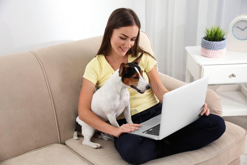 Härlig kvinna med hennes hundarbete på bärbara datorn arkivbilder
