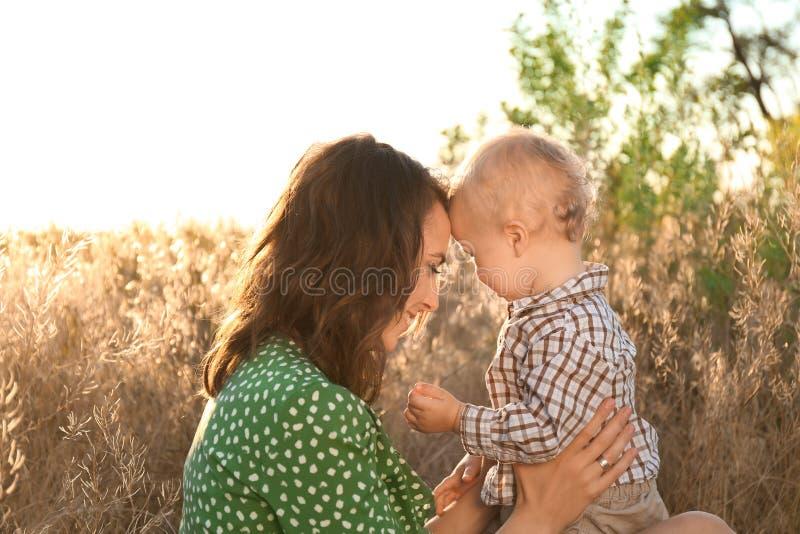 Härlig kvinna med hennes lilla son i bygd på solig dag arkivfoto