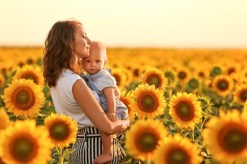 Härlig kvinna med hennes lilla son i solrosfält på solig dag fotografering för bildbyråer
