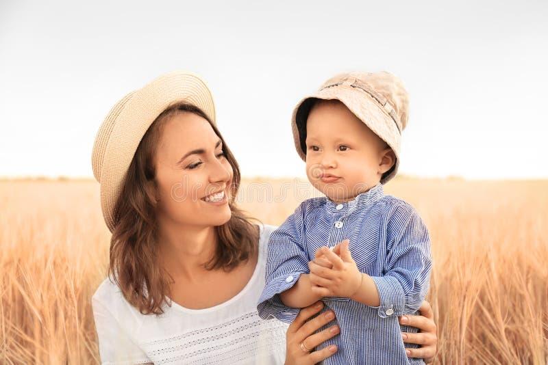 Härlig kvinna med hennes lilla son i vetefält på sommardag royaltyfria foton