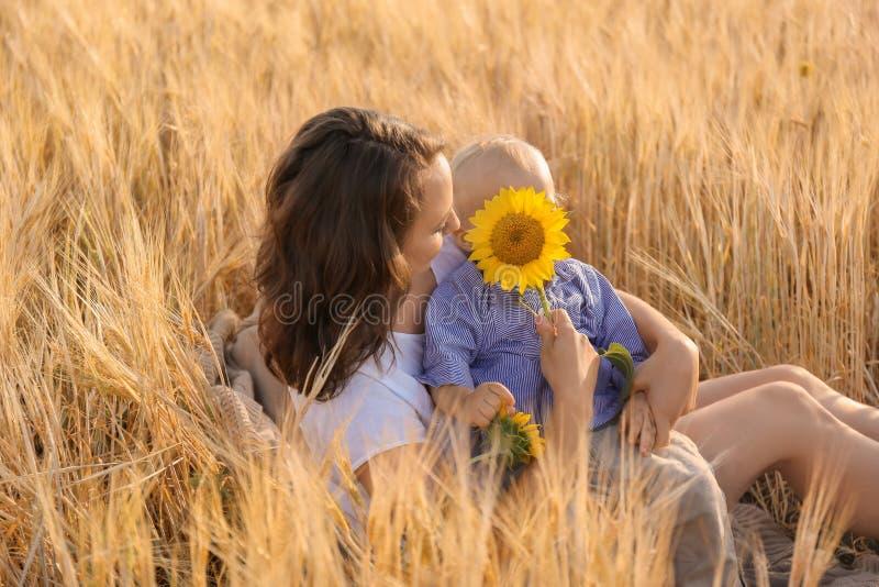 Härlig kvinna med hennes lilla son i vetefält på sommardag arkivbild