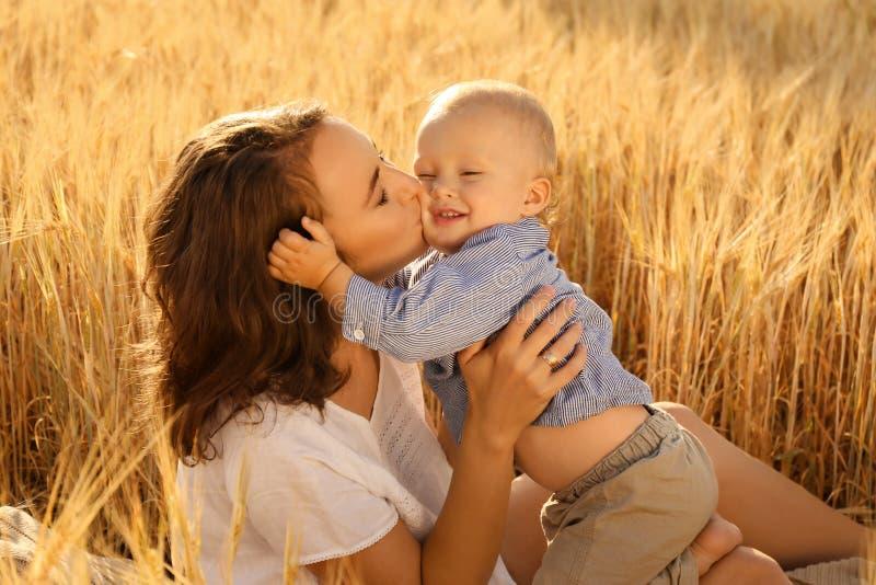 Härlig kvinna med hennes lilla son i vetefält på sommardag arkivbilder