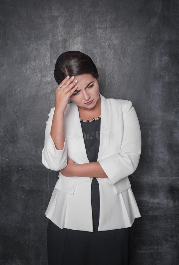 Härlig kvinna med huvudvärk på svart tavla royaltyfria foton