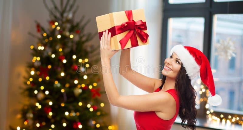 Härlig kvinna med julgåvan hemma arkivfoton